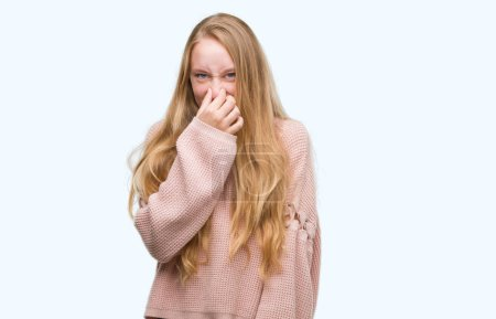 Blonde teenager woman wearing pink sweater smelling something stinky and disgusting, intolerable smell, holding breath with fingers on nose. Bad smells concept.