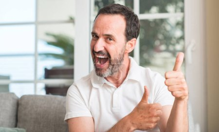 Handsome middle age man happy with big smile doing ok sign, thumb up with fingers, excellent sign