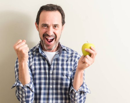 Photo for Senior man holding a green apple screaming proud and celebrating victory and success very excited, cheering emotion - Royalty Free Image