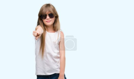 Photo for Young blonde toddler wearing sunglasses pointing with finger to the camera and to you, hand sign, positive and confident gesture from the front - Royalty Free Image