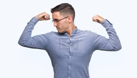 Handsome young elegant man wearing glasses showing arms muscles smiling proud. Fitness concept.