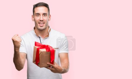 Handsome young man giving a present screaming proud and celebrating victory and success very excited, cheering emotion