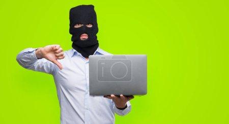 Homme d'affaires hacker tenant un ordinateur portable avec le visage en colère, négatif signe montrant n'aime pas avec les pouces vers le bas, notion de rejet