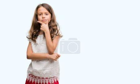 Photo pour Brunette fille hispanique regardant avec confiance la caméra avec le sourire avec les bras croisés et la main levée sur le menton. Penser positif . - image libre de droit