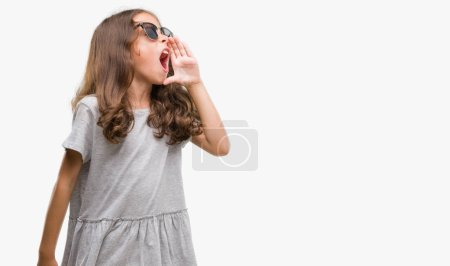 Brunette hispanic girl wearing sunglasses shouting and screaming loud to side with hand on mouth. Communication concept.