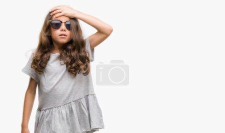 Brunette hispanic girl wearing sunglasses surprised with hand on head for mistake, remember error. Forgot, bad memory concept.