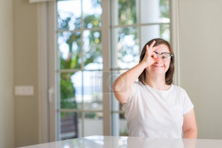 Down syndrome woman at home with happy face smiling doing ok sign with hand on eye looking through fingers