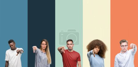 Group of people over vintage colors background looking unhappy and angry showing rejection and negative with thumbs down gesture. Bad expression.