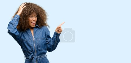 Photo for African american woman wearing blue jumpsuit pointing away side with finger - Royalty Free Image