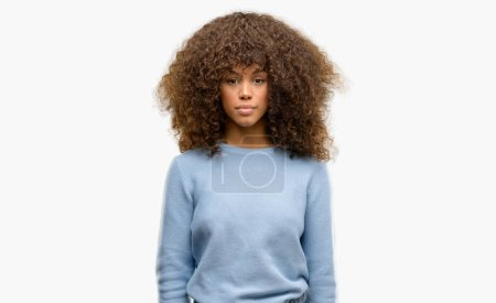 African american woman wearing a sweater with serious expression on face. Simple and natural looking at the camera.