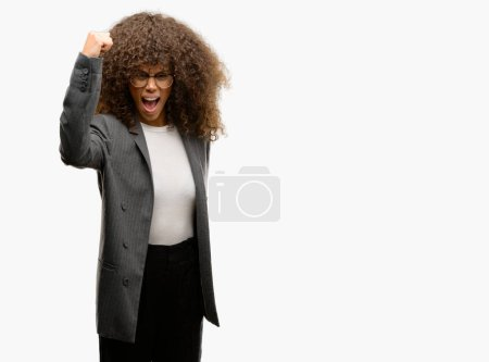 African american business woman wearing glasses angry and mad raising fist frustrated and furious while shouting with anger. Rage and aggressive concept.