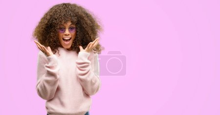Photo for African american woman wearing a pink sweater very happy and excited, winner expression celebrating victory screaming with big smile and raised hands - Royalty Free Image