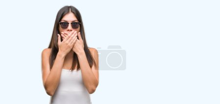 Young beautiful hispanic wearing sunglasses shocked covering mouth with hands for mistake. Secret concept.