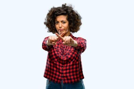 Mujer árabe hermosa molesta con mala actitud haciendo señal de stop con la mano, diciendo que no, expresando seguridad, defensa o restricción, tal vez empujando