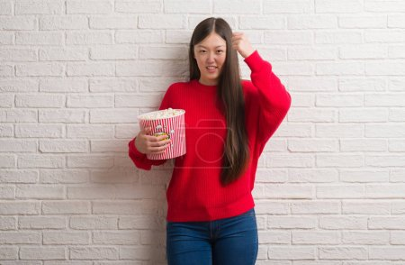 Young Chinese woman over brick wall eating pop corn annoyed and frustrated shouting with anger, crazy and yelling with raised hand, anger concept