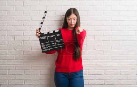 Photo pour Jeune femme chinoise sur mur de briques blanches tenant clin d'oeil pointant avec le doigt vers la caméra et à vous, signe de la main, geste positif et confiant de l'avant - image libre de droit