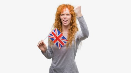 Young redhead woman holding flag of United Kingdom annoyed and frustrated shouting with anger, crazy and yelling with raised hand, anger concept