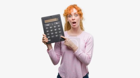 Young redhead woman holding big calculator scared in shock with a surprise face, afraid and excited with fear expression