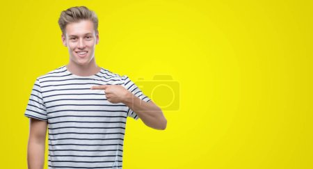 Young handsome blond man wearing stripes sailor t-shirt with surprise face pointing finger to himself