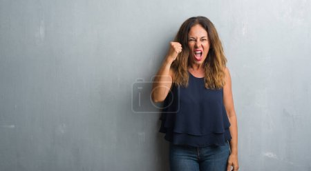 Middle age hispanic woman standing over grey grunge wall angry and mad raising fist frustrated and furious while shouting with anger. Rage and aggressive concept.