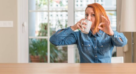 Redhead woman holding a cup of coffee doing ok sign with fingers, excellent symbol