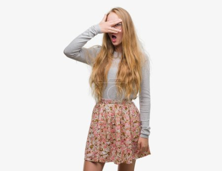 Blonde teenager woman wearing flowers skirt peeking in shock covering face and eyes with hand, looking through fingers with embarrassed expression.