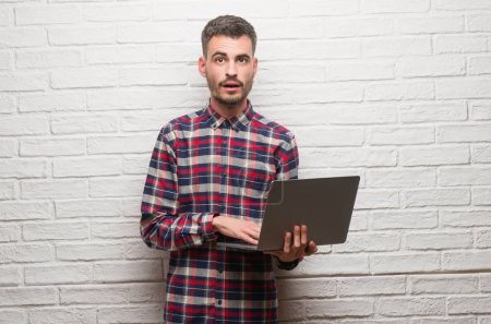 Young adult man over brick wall using laptop scared in shock with a surprise face, afraid and excited with fear expression