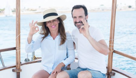 Middle age couple traveling on sailboat doing ok sign with fingers, excellent symbol