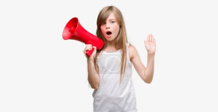Photo for Young blonde toddler holding megaphone very happy and excited, winner expression celebrating victory screaming with big smile and raised hands - Royalty Free Image