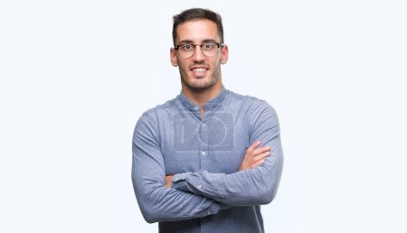 Handsome young elegant man wearing glasses happy face smiling with crossed arms looking at the camera. Positive person.