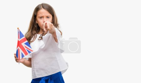 Brunette hispanic girl holding flag of United Kingdom pointing with finger to the camera and to you, hand sign, positive and confident gesture from the front
