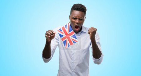 Young african american man holding United Kingdom flag annoyed and frustrated shouting with anger, crazy and yelling with raised hand, anger concept