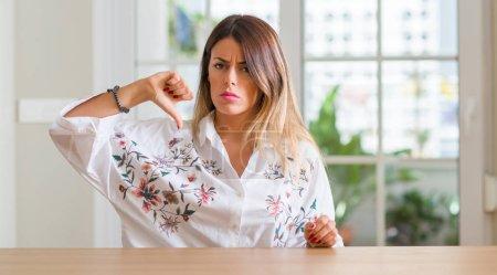 Foto de Mujer joven en casa con cara enfadada, negativo muestra que muestra aversión con los pulgares hacia abajo, el concepto de rechazo - Imagen libre de derechos