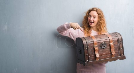 Young redhead woman holding vintage chest very happy pointing with hand and finger