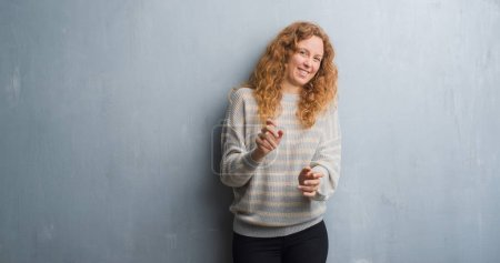Young redhead woman over grey grunge wall disgusted expression, displeased and fearful doing disgust face because aversion reaction. With hands raised. Annoying concept.