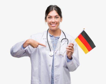 Photo pour Jeune médecin hispanique femme tenant drapeau de l'Allemagne avec visage surprise pointant du doigt vers lui-même - image libre de droit