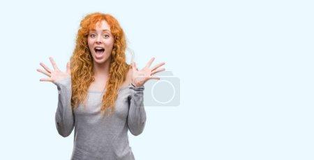 Photo pour Femme rousse jeune célébrant fou et étonné du succès avec les bras élevés et yeux ouverts cris excités. Concept gagnant - image libre de droit