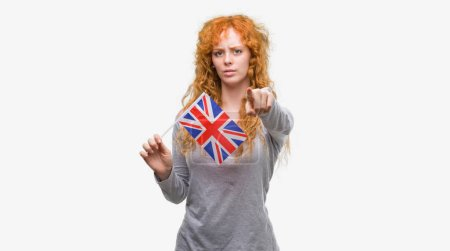 Young redhead woman holding flag of United Kingdom pointing with finger to the camera and to you, hand sign, positive and confident gesture from the front