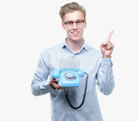 Young handsome blond man holding vintage telephone very happy pointing with hand and finger to the side