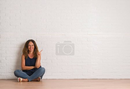 Middle age hispanic woman sitting on the floor ove...
