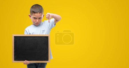 Photo pour Petit enfant aux cheveux foncés tenant un tableau noir avec un visage en colère, signe négatif déplaisant avec les pouces baissés, concept de rejet - image libre de droit