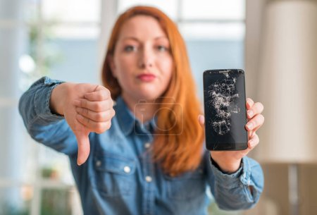 Photo for Redhead woman holding broken smartphone with angry face, negative sign showing dislike with thumbs down, rejection concept - Royalty Free Image