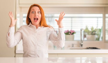 Photo for Redhead woman at kitchen celebrating crazy and amazed for success with arms raised and open eyes screaming excited. Winner concept - Royalty Free Image