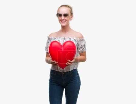 Blonde teenager woman holding red heart with a happy face standing and smiling with a confident smile showing teeth