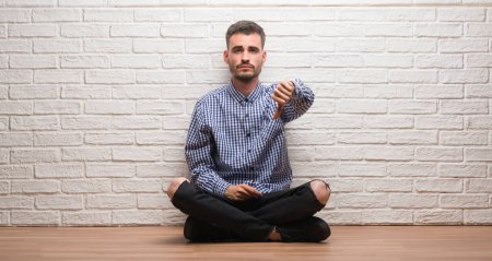 Young adult man sitting over white brick wall looking unhappy and angry showing rejection and negative with thumbs down gesture. Bad expression.