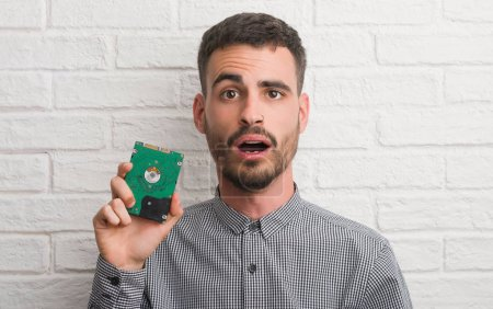 Young adult man over brick wall holding hard drive scared in shock with a surprise face, afraid and excited with fear expression