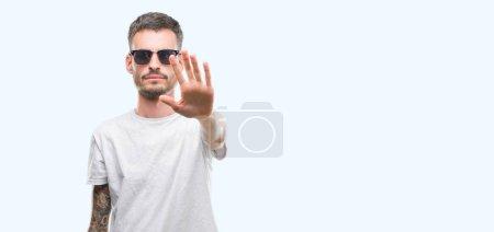 Photo pour Young tatoué adulte homme lunettes de soleil avec la main ouverte, faisant signe d'arrêt avec l'expression grave et confiante, geste de défense - image libre de droit