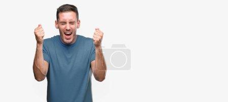 Photo pour Beau jeune homme casual exhalté succès avec bras soulevés célébrant victoire souriant. Concept gagnant. - image libre de droit