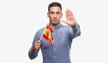Photo pour Beau jeune homme tenant un drapeau de l'Espagne avec main faisant signe d'arrêt avec l'expression grave et confiante, geste de défense ouverte - image libre de droit