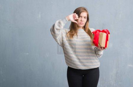 Foto de Adulto joven sobre pared gris grunge con un presente con cara enfadada, signo negativo que muestra aversión con los pulgares hacia abajo, concepto de rechazo - Imagen libre de derechos